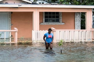 A woman walks in a flooded street after the effects of Hurricane Dorian arrived in Nassau, Bahamas, September 2, 2019.