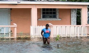 A woman walks in a flooded street after the effects of Hurricane Dorian arrived in Nassau, Bahamas.