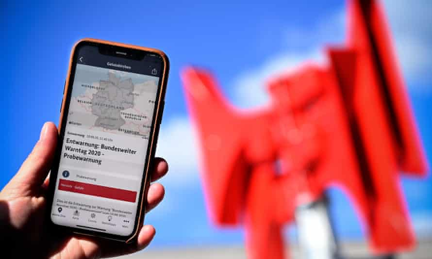 A smartphone displays the Nina app in front of the red horns of a warning siren in Leverkusen.