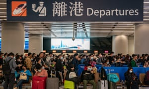 Travellers wearing face masks queue in West Kowloon station, Hong Kong