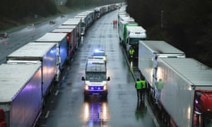 Police cars passing by lorries queueing on M20 motorway to enter the port of Dover