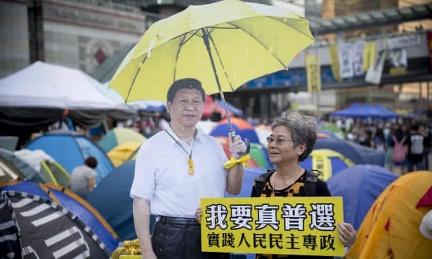 A woman poses with a sign reading 'we want universal suffrage' next to a cardboard cutout of Xi Jinping holding a yellow umbrella – the symbol of Hong Kong's pro-democracy movement – during a protest in 2014.