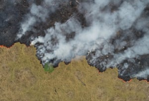 An aerial view shows smoke rising over a deforested plot of the rainforest in Porto Velho.