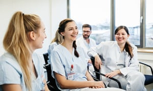 A group of medical students laughing with each other during a teaching seminar at the hospital.