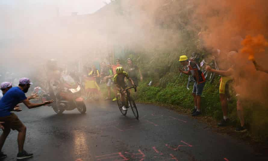 Simon Yates leads the race as as smoke from fans billows in the last kilometers during the fifteenth stage between Limoux and Foix Prat d'Albis.