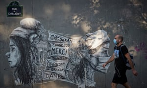 A Parisian walks past street art on the corner of Saint-Anthoine Hospital in Paris, thanking Hospital workers for their work under Covid-19 pandemic