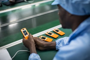 An employee works on a mobile phone on the assembly line at a factory in Brazzaville