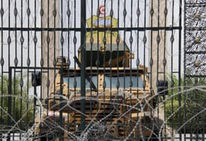 Barbed wire and a military armored personnel carrier block a side entrance of the Tunisian parliament in Tunis.