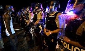 A protester stands facing a police line shortly before shots were fired in Ferguson.