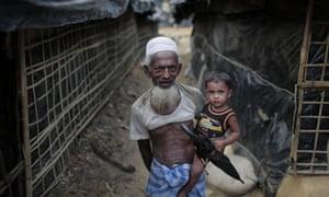 A Rohingya man carries his grandson in a camp for Rohingya people in Ukhiya, near Cox's Bazar, Bangladesh.