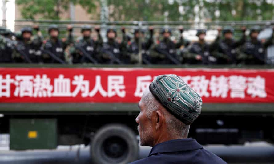 A Uighur man looks on at a truck carrying paramilitary police officers in Urumqi, Xinjiang.