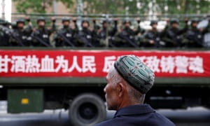 A truck carrying paramilitary policemen passes a Uighur man during an anti-terrorism oath-taking rally in Urumqi, Xinjiang.