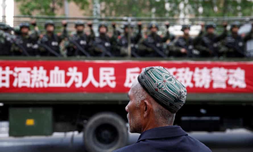 A truck carrying paramilitary policemen passes a Uighur man during an anti-terrorism oath-taking rally in Urumqi, Xinjiang.