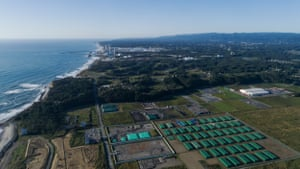 Aerial view of a nuclear waste storage area in Futaba, with the Fukushima Daiichi nuclear power plant in the background.