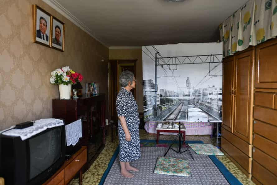 Japanese wife , Yoshie looks at the print of photograph of the neighborhood Yoshie lived in Tokyo before she left Japan in 1960. Pyongyang. North Korea.