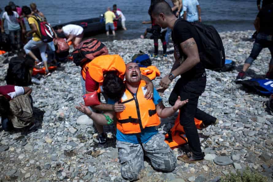 A Syrian refugee prays after arriving on Lesbos in September 2015.