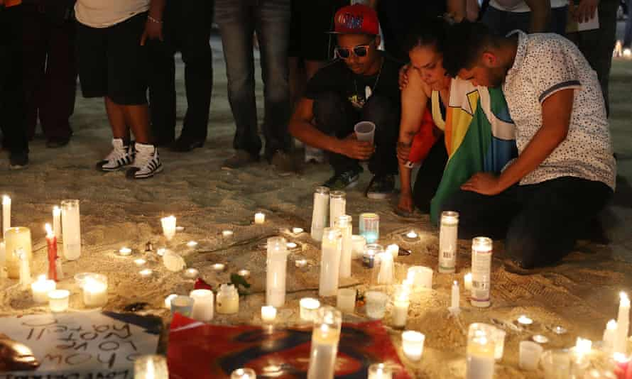 Mourners pay their respects at a memorial for the shooting victims.