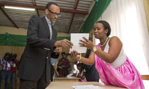 Rwanda President Paul Kagame is guided by polling assistants as he votes in Rwanda's capital Kigali.