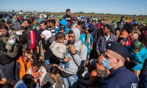 Syrian refugees in field, with police