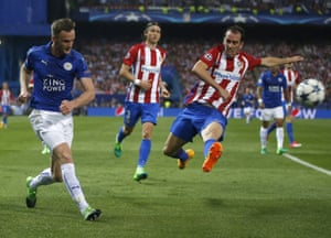 Leicester City's Andy King, left, hits a cross as Atletico's Koke attempts to block.