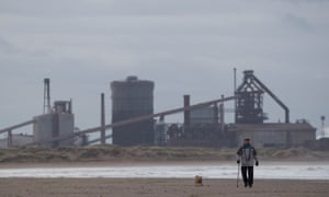 A man walks his dog on the beach in front of the former SSI steelmaking plant in Redcar