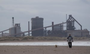 A man walks his dog on a beach in Redcar