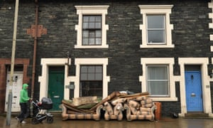 A resident walks past furniture placed outside a house in Keswick.
