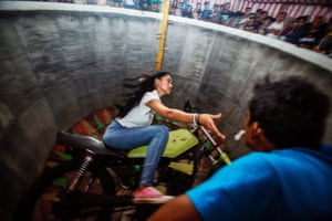 Purba reaches for a tip from a spectator as she rides around the wall