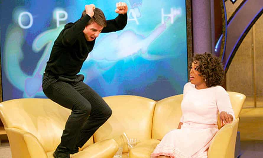 Tom Cruise standing with his arms raised at one end of a three-seat sofa, with Winfrey looking shocked at the other end.