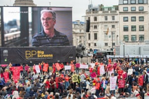 a crowd of activists in front of a big screen