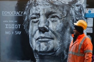 A construction worker stands in front of a piece of street art portraying Donald Trump.