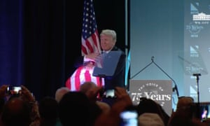 Donald Trump hugs the US flag after his speech to NFIB conference.