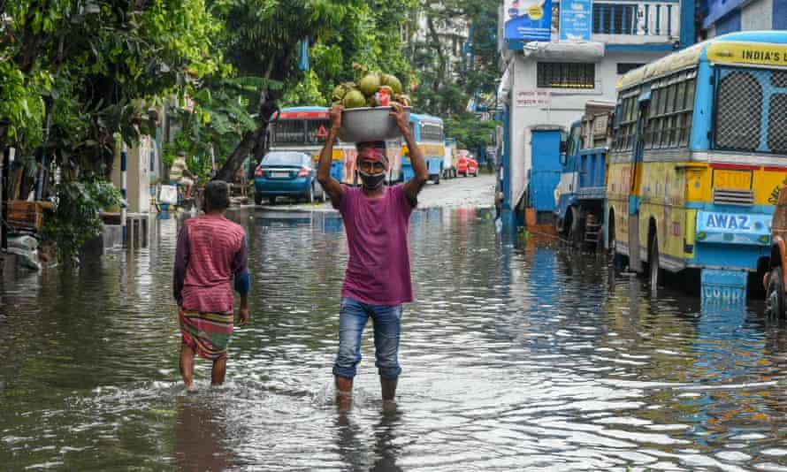 People in a flooded street in Kolkata