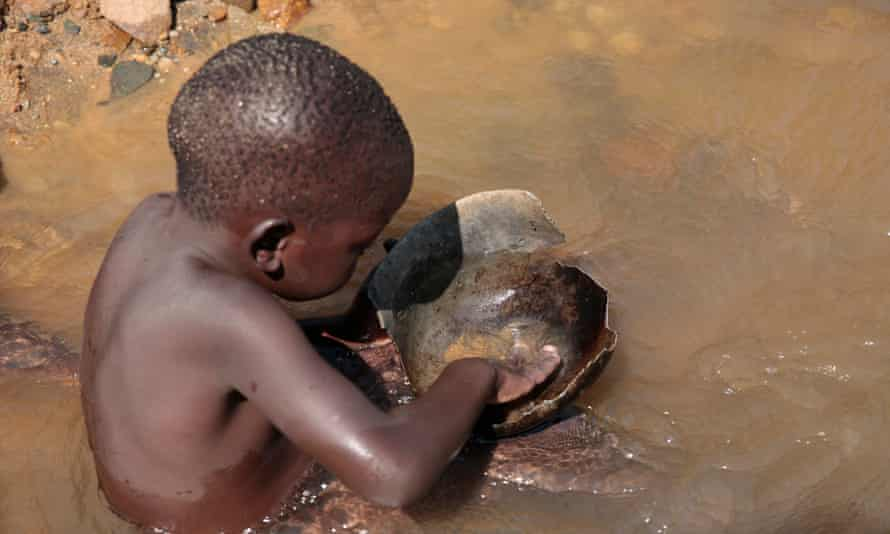 Five-year-old Desire Matanda uses a pan to search for particles of gold along the Odzi River in Mutare. Poverty has forced many children in Zimbabwe out of school and into work.