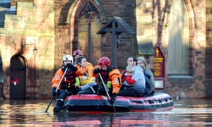 Rescuers paddle a dinghy through Carlisle after Storm Desmond in 2015