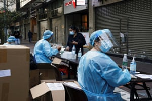 A medical worker in a protective suit helps a resident to register at a makeshift community testing centre at Jordan residential area, in Hong Kong on Friday.