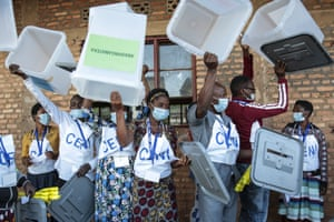 Giheta, Burundi. Electoral officials hold up ballot boxes to show they are empty before voters cast their votes in the presidential election. President Nkurunziza is stepping aside after a divisive 15-year rule