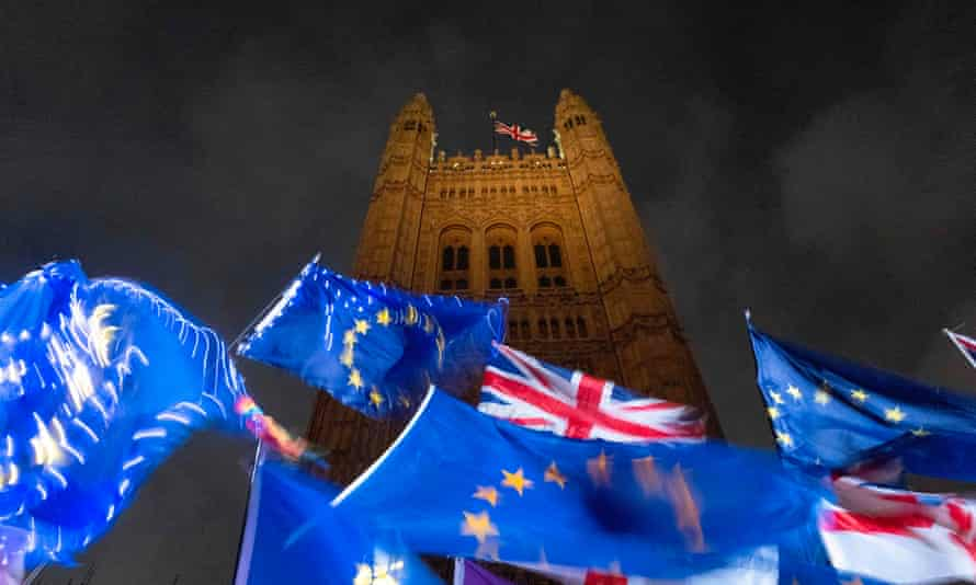 EU and Union flags flutter in the breeze outside of the Houses of Parliament in central London.