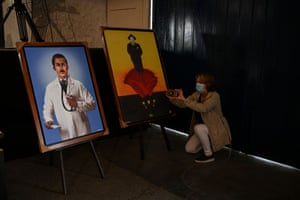 A woman takes pictures of Hernández paintings in the chapel of La Salle College High School during the preparations for the beatification ceremony