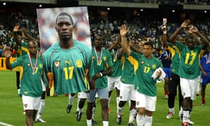 Cameroon team players carry a giant portrait of their late team mate Marc-Vivien Foe. Foe died after collapsing on the pitch during their match against Colombia.
