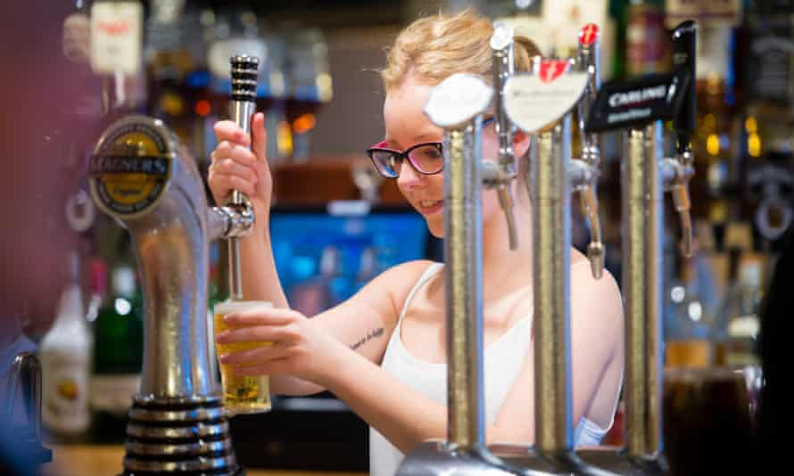 a young woman pours a pint of cider in a pub