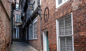 An old sign for a cordwainer (shoemaker) is high up on a wall, down the narrow alley of Lady Peckett's Yard, York