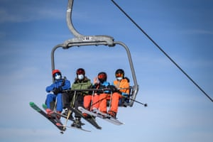 Skiers wearing protective face masks against the spread of the Covid-19 ride a ski lift in Verbier.