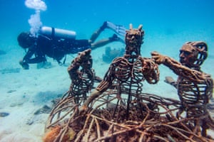 Koh Tao, ThailandA diver swims next to metal figures set up on an artificial reef for marine conservation