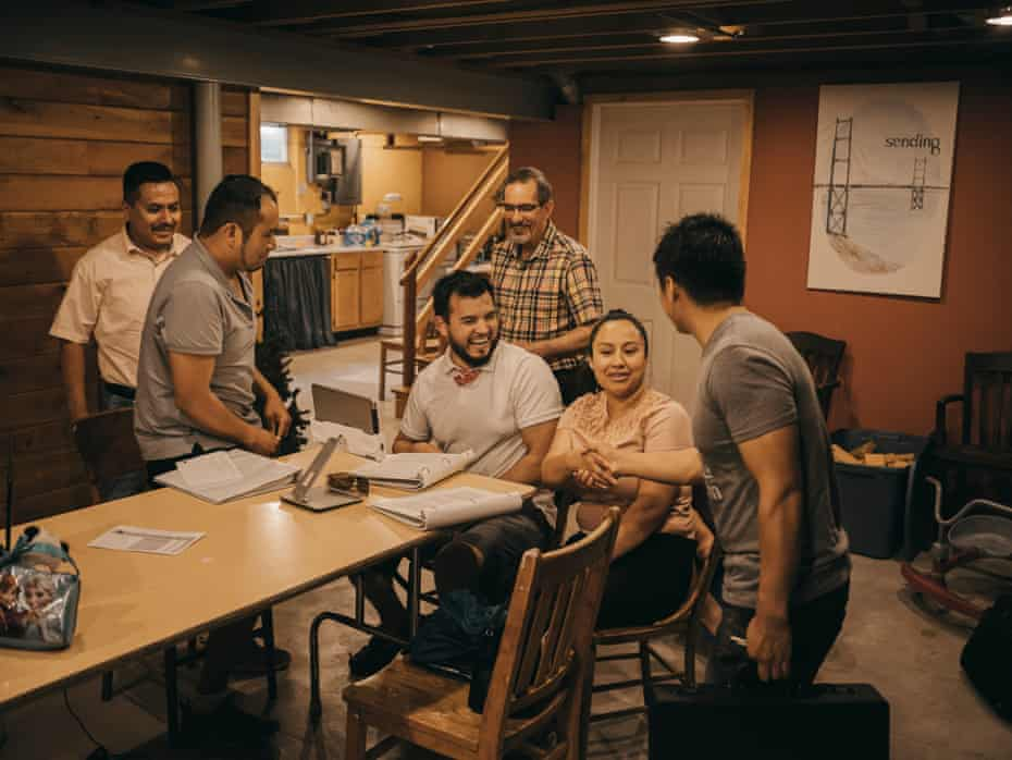 A group of four Latino men and one woman congregate around a dining table in a house. One white man, pastor Dan Krahenbuhl, stands in the background.