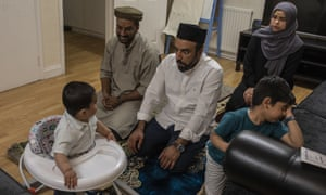 Imam Raza Ahmed pulls a face at his son, Daud, as the family pray at their home in London during Ramadan
