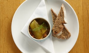 Brown shrimps in spiced butter in a small round bowl on a plate with two slices of brown bread