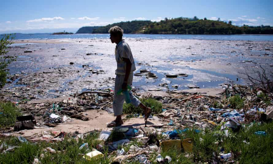 A man walks along the shoreline of the polluted waters of Guanabara Bay.