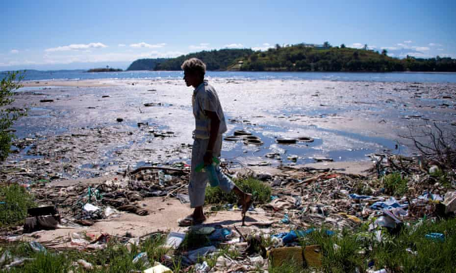 A man walks along the shoreline of the polluted waters of Guanabara Bay near Rio de Janeiro
