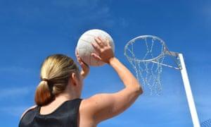 Woman shooting into netball net